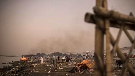 Two bodies were partially burnt, police said on Sunday. In picture - Funeral pyres burn, amid mass cremations of Covid-19 fatalities, on the banks of the Yamuna river.(Bloomberg | Representational image)