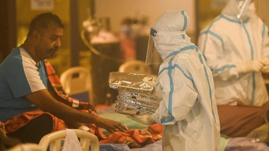 Health workers wearing personal protective equipment (PPE kit) attends to Covid-19 coronavirus positive patients inside a banquet hall temporarily converted into a covid care centre in New Delhi.(AFP)