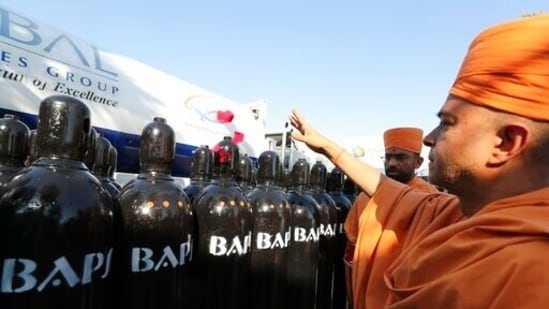 The head of BAPS Shri Swaminarayan Mandir in Abu Dhabi throws rose petals before shipping hundreds of liquid oxygen cylinders to India.(AP)