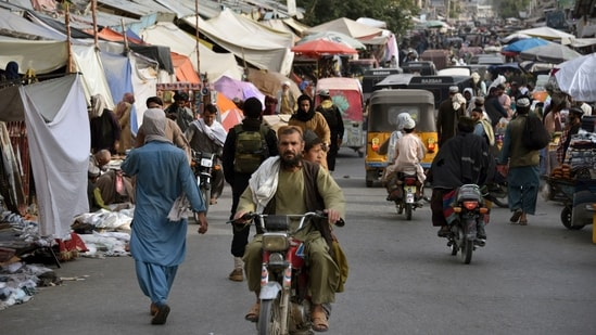People make their way along a market area in Kandahar.(AFP)