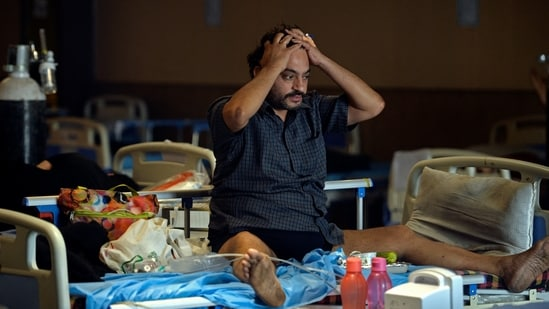 A Covid-19 coronavirus patient reacts while sitting on a bed inside a banquet hall temporarily converted into a Covid care centre in New Delhi on May 10, 2021. (AFP)