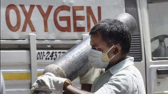 New Delhi: A family member of a COVID-19 patient carries oxygen cylinder from an oxygen filling centre in New Delhi, Saturday, May 8, 2021. (PTI Photo/Kamal Singh)(PTI05_08_2021_000160B) (PTI)