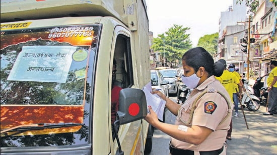 A police official checks for e-passes in Pune. Lockdown violators without proper e-passes were fined. (Ravindra Joshi)