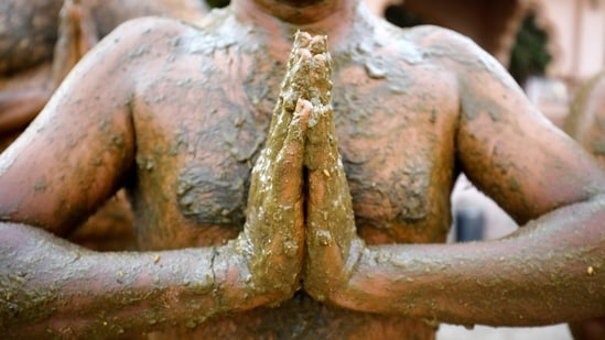 """Uddhav Bhatia, a frontline worker, prays after applying cow dung on his body during """"cow dung therapy"""", believing it will boost his immunity to defend against the coronavirus disease (Covid-19) at the Shree Swaminarayan Gurukul Vishwavidya Pratishthanam Gaushala or cow shelter on the outskirts of Ahmedabad, India, May 9, 2021. Picture taken May 9, 2021. (REUTERS)"""