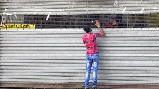A vendor selling liquor from a partially drawn shutter in Ludhiana on Wednesday. (Gurpreet Singh/HT)