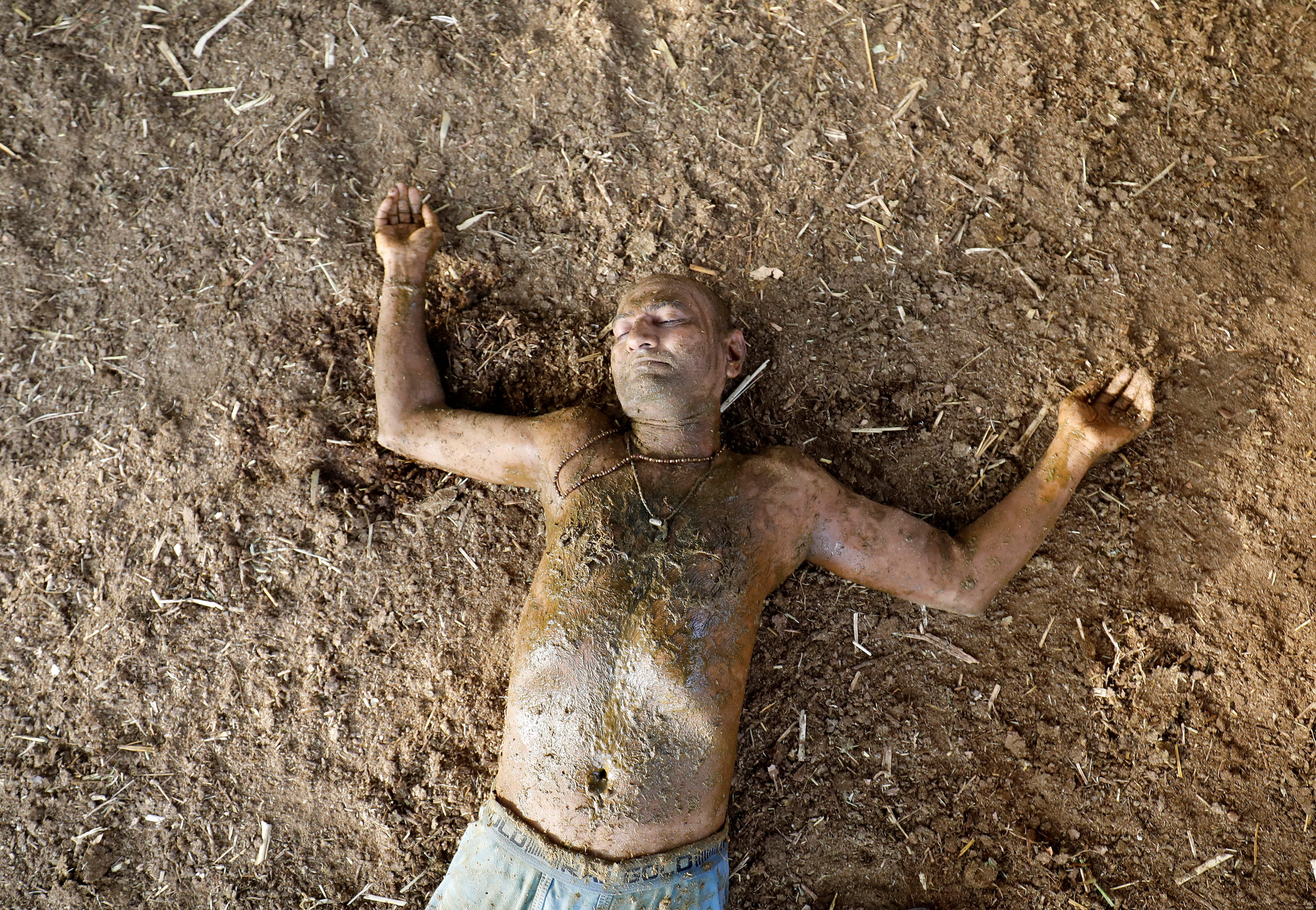 """Ashok Oza lies on the ground after applying cow dung on his body during """"cow dung therapy"""", believing it will boost his immunity to defend against the coronavirus disease (Covid-19) at the Shree Swaminarayan Gurukul Vishwavidya Pratishthanam Gaushala or cow shelter on the outskirts of Ahmedabad, India, May 9, 2021."""