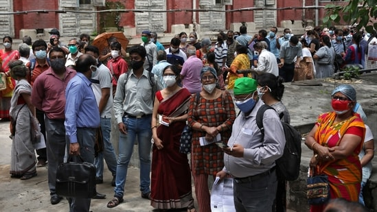 People wearing protective face masks wait to receive their second dose of Covishield.(REUTERS)