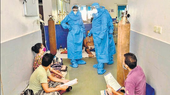 Goa CM Pramod Sawant (left), wearing a PPE suit, speaks to Covid-19 patients at the Goa Medical College, in Panjim. (AFP)