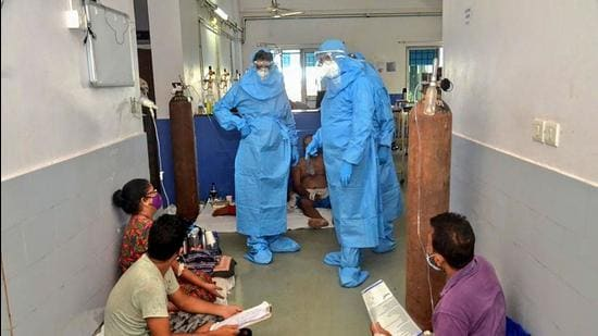 Goa chief minister Pramod Sawant (L), wearing a personal protective equipment suit, speaks to Covid-19 patients on May 11 at the Goa Medical College and Hospital, in Panaji after 26 people died in the hospital. (File photo)