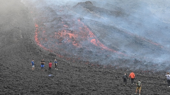 People watch as lava flows from Guatemala's Pacaya Volcano at the Cerro Chino hill in San Vicente Pacaya municipality, Guatemala. (AFP)