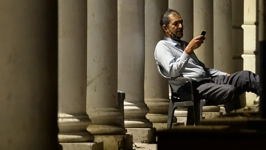 A man checks his mobile phone while sitting in a deserted shopping arcade during a lockdown imposed by the government amidst rising Covid-19 coronavirus cases in New Delhi.(AFP)