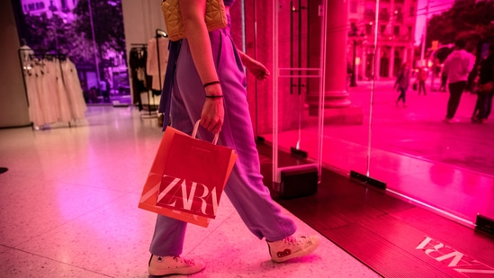 A customer carrying branded shopping bags departs a Zara store, operated by Inditex SA, in Barcelona, Spain, on Wednesday, May 12, 2021.(Bloomberg)
