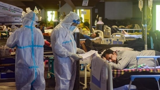 Health workers inspect Covid-19 patients undergoing treatment at Shehnai Banquet Hall, converted into an isolation centre amid surge in cases in New Delhi. (PTI file photo)