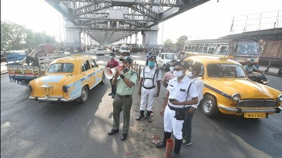 Police personnel announce about Covid-19 protocols after the West Bengal government declared lockdown in Kolkata on Saturday. (PTI PHOTO.)