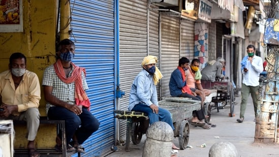 Workers seen outside shuttered shops at Khari Baoli during the Covid-19 induced lockdown, in New Delhi.(Sanjeev Verma/HT PHOTO)