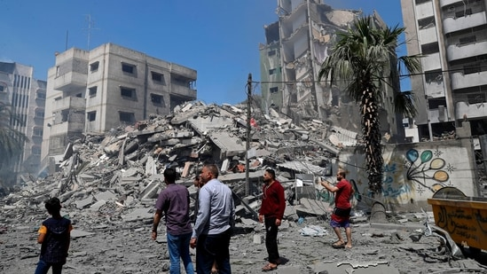 People insect the the rubble of the Yazegi residential building that was destroyed by an Israeli airstrike, in Gaza City.(AP)