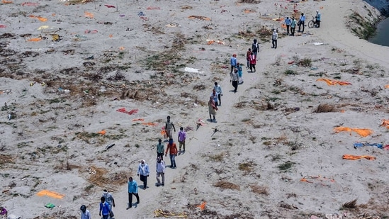 Family members and relatives return after burying a dead body, near the banks of river Ganga at Phaphamau Ghat in Prayagraj, Sunday, May 16, 2021. (PTI)