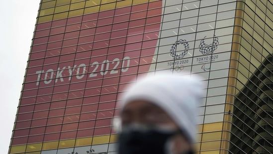 A man wearing a protective mask to help curb the spread of the coronavirus walks near a banner of the Tokyo 2020 Olympics and Paralympics.(AP)