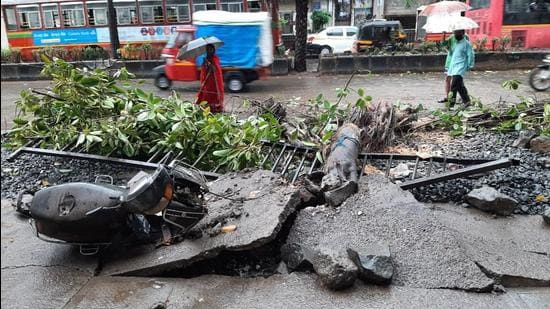 A two-wheeler was damaged when a tree fell on it due to the strong winds, in Thane on Monday, May 17. (Praful Gangurde/ HT photo)