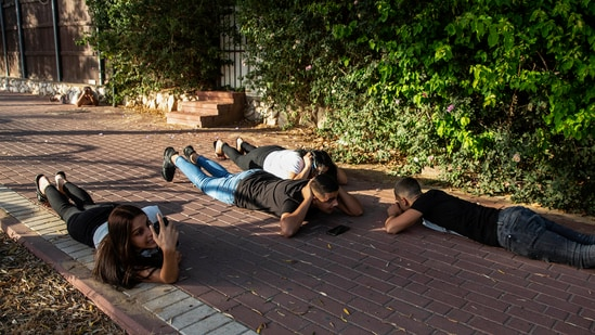 Israelis take cover as a siren sounds a warning of incoming rockets fired from the Gaza Strip, in Ashkelon, southern Israel.(AP)