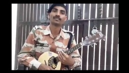 The image shows constable Rahul Khosla playing the mandolin.