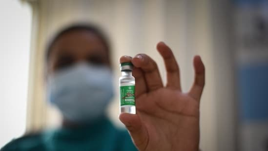 A health worker holds up a vial of Covishield at PSRI Hospital in New Delhi.(HT Photo)
