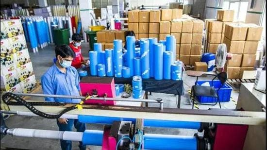 A worker wearing operating a tape cutting machine while producing adhesive sealing tapes at a factory in Sonepat district. (Bloomberg file photo)