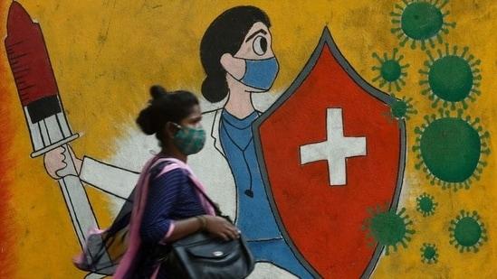 A woman walks past a graffiti dedicated to the frontline wokers battling the raging coronavirus pandemic on a street in Mumbai. (REUTERS)