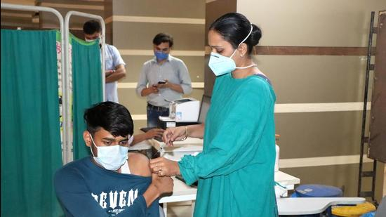 A medical professional administers an anti-Covid vaccine to a youth at Rohtak PGIMS. (HT file)