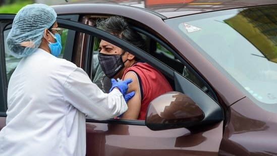 A health worker administers a dose of the Covid-19 vaccine at a drive-through vaccination camp at a mall in Noida,(PTI)