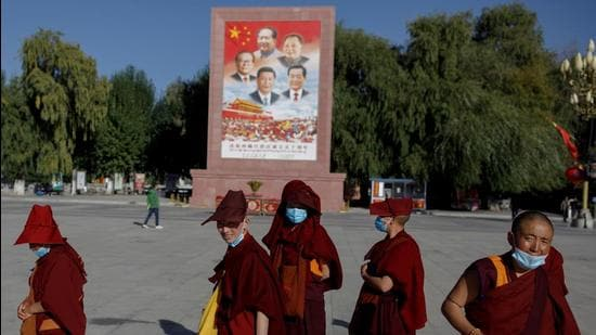 In this file photo, Buddhist nuns walk past a poster showing Chinese President Xi Jinping and former Chinese leaders Jiang Zemin, Mao Zedong, Deng Xiaoping and Hu Jintao in Potala Palace square in Lhasa, Tibet Autonomous Region, China. (REUTERS)