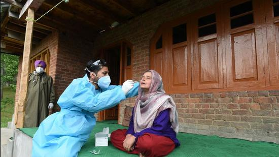 A health worker takes a nasal swab sample of a woman to test for Covid-19 outside her home at Khag in central Kashmir's Budgam district. (HT file)