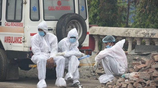 Health workers take a break from cremating the deceased, during the second wave of coronavirus, in New Delhi.(PTI)