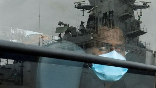A man who was stranded at sea aboard Barge P305 due to Cyclone Tauktae looks out of a bus window after he was rescued by the Indian Navy aboard the Indian Naval Ship (INS) Kochi, at Naval Dockyard, in Mumbai, India.(Reuters)