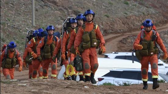 In this photo provided by China's Xinhua News Agency, rescuers walk into the accident site to search for survivors in Jingtai County of Baiyin City, northwest China's Gansu province, on Sunday. (AP)