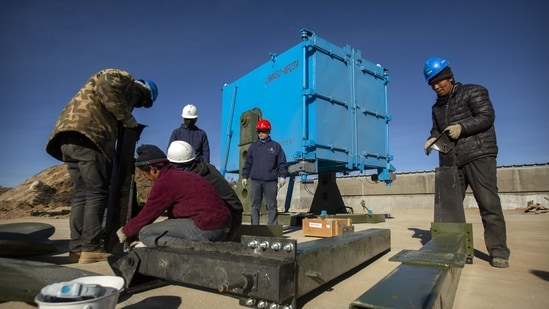 In this representative photo, construction workers prepare to install one of 18 wide-field air telescopes at an observatory at Haizi Mountain near Daocheng in southwestern China's Sichuan Province. (AP Photo)