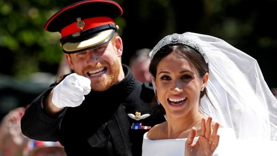 Britain's Prince Harry gestures next to his wife Meghan as they ride a horse-drawn carriage after their wedding ceremony at St George's Chapel in Windsor Castle in Windsor, Britain, May 19, 2018.(REUTERS)