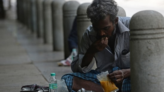 A man eats free food being distributed by a voluntary humanitarian organisation to the needy people in Chennai on May 24, 2021.(AFP)