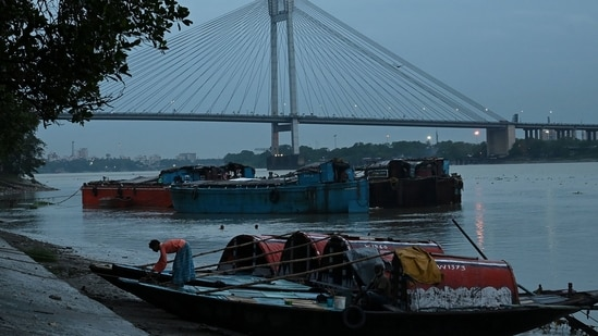 A man ties a boat on the side of the Ganga river in view of the upcoming Cyclone Yaas as rain clouds loom over the sky of Kolkata on May 24, 2021. (AFP)