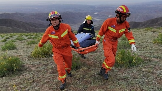 Rescue workers carry a stretcher as they work at the site where extreme cold weather killed participants of a 100-km ultramarathon race in China(VIA REUTERS)