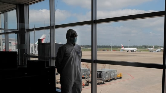 A Sri Lankan airport worker in protective suit stands inside a terminal at the Katunayake International Airport in Colombo, Sri Lanka (AP).