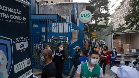 People wait in line outside a community medical center to get a shot of the Pfizer vaccine for Covid-19 in Sao Paulo, Brazil (AP).