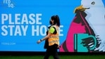 FILE PHOTO: An essential worker walks past a 'Please Stay Home' sign on the first day of a five-day lockdown implemented in the state of Victoria.(REUTERS)