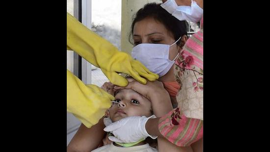 A health worker collecting swab samples of a child for Covid testing in Ludhiana on Thursday. (Gurpreet Singh/HT)