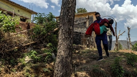 Pramila Devi, 36, who is suffering from the coronavirus disease (Covid-19), is carried by her nephew Rajesh Kumar, as he takes her to a local government dispensary, in Kaljikhal, in Uttarakhand.(Reuters)