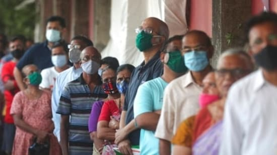 People wearing face masks as a precaution against the Covid-19 line up to receive the vaccine in Mumbai(AP)