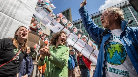 Members of the environmental group MilieuDefensie celebrate the verdict of the Dutch environmental organisation's case against Royal Dutch Shell Plc, outside the Palace of Justice courthouse in The Hague.(Bloomberg)