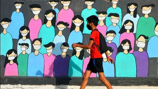 A boy walks past a graffiti raising awareness about Covid-appropriate behaviour at Airoli in Mumbai on Wednesday, May 26. (Satish Bate/HT photo)