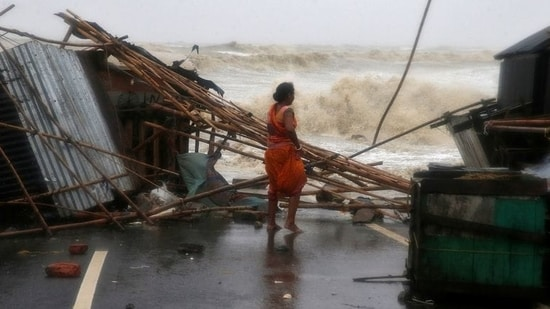 A woman stands next to her stall damaged by heavy winds due to Cyclone Yaas in Odisha's Balasore district.(Rupak De Chowdhuri / REUTERS)