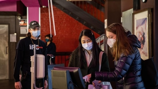 Guests wearing protective masks use a kiosk to purchase tickets at IFC Center movie theatre amid the coronavirus disease (Covid-19) pandemic in the Manhattan borough of New York City.(REUTERS)